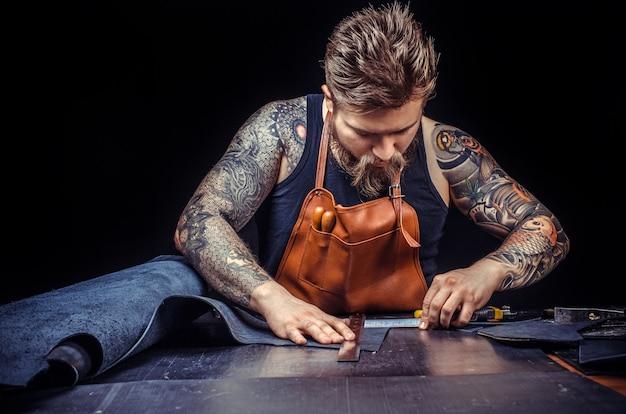 Человек, работающий с кожей, создает в своем магазине качественный продукт из кожи.