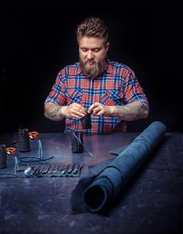 Человек, работающий с кожаной надписью с кожаными изделиями на своем рабочем месте.