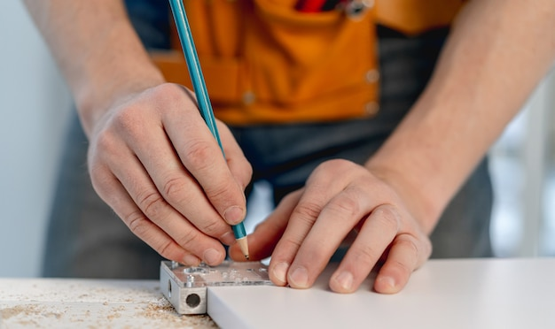 Man working with pencil marking holes during process of wooden furniture manufacturing in workshop