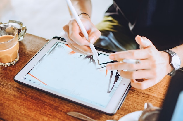 ポータブルタブレットコンピューターで作業している人。軽いモダンなオフィスでデジタルプランを描くデザイナー。水平。背景がぼやけている。