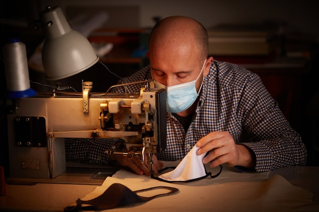 Человек, работающий на швейной машине, делает самодельную маску для лица для предотвращения и остановки распространения вируса короны
