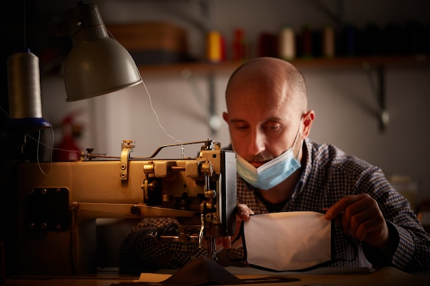 Man working with sewing machine doing homemade face mask for preventing and stop corona virus spreading