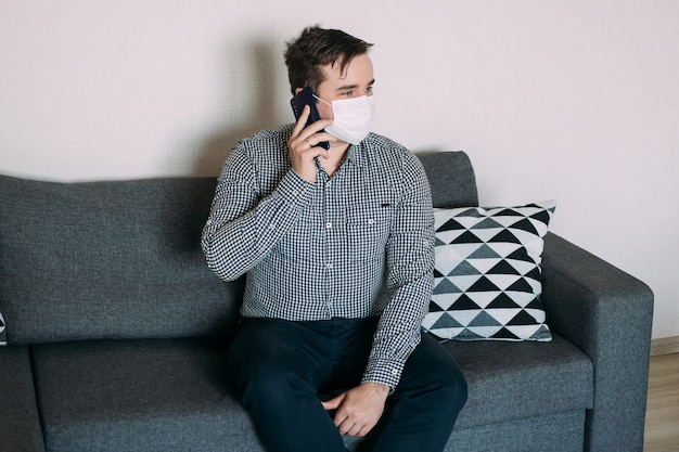Man working with smartphone working from home office wearing mask