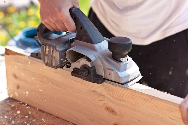 Человек, работающий с инструментами и деревянными досками
