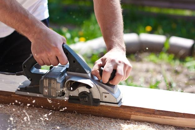 ツールと木の板で作業する男