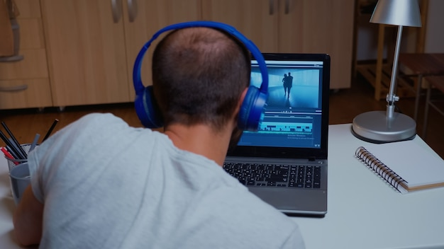 最新のソフトウェアを使用してラップトップでビデオ映像を操作する男。真夜中にモダンなキッチンの机の上に座っているプロのラップトップでオーディオフィルムモンタージュを編集するビデオグラファー