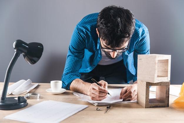 机の上で木製の立方体を扱う男
