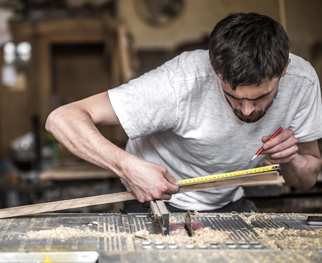 機械で木製品を扱う男