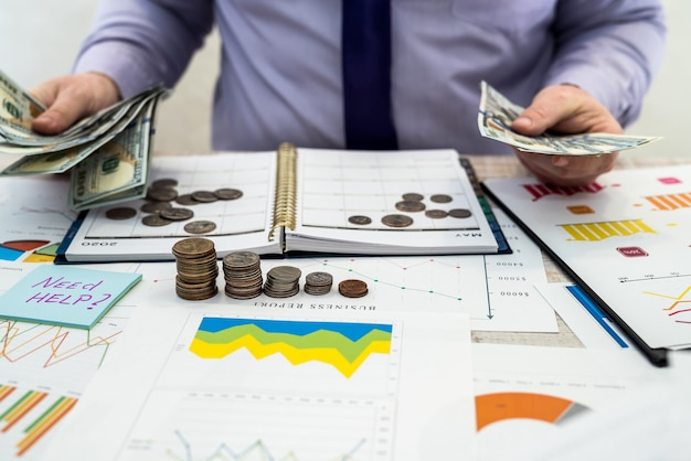 A man works and calculates company profits from the sale or lease of goods or services and office using charts and chart documents, dollars and pennies