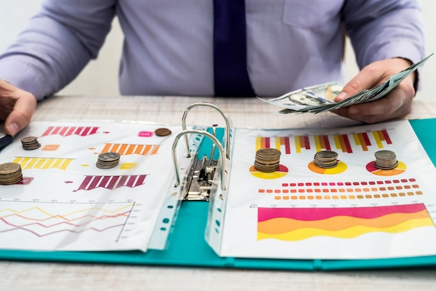 A man works and calculates company profits from the sale or lease of goods or services and office using charts and chart documents
