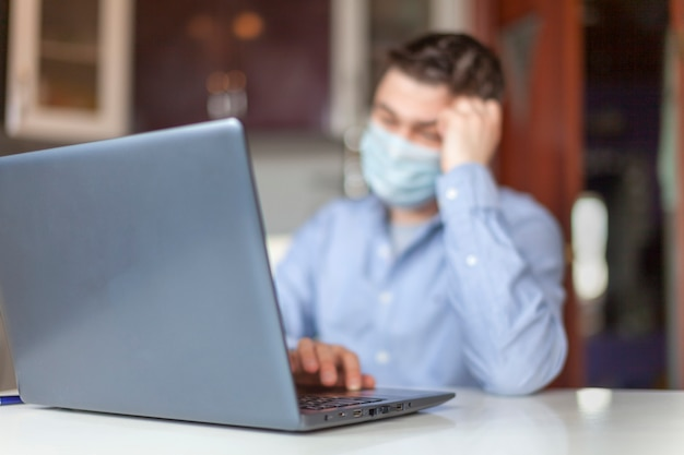 A man works from home on a laptop. young man in protective respiratory mask against a virus. a businessman is sitting at a table in the kitchen. coronavirus concept