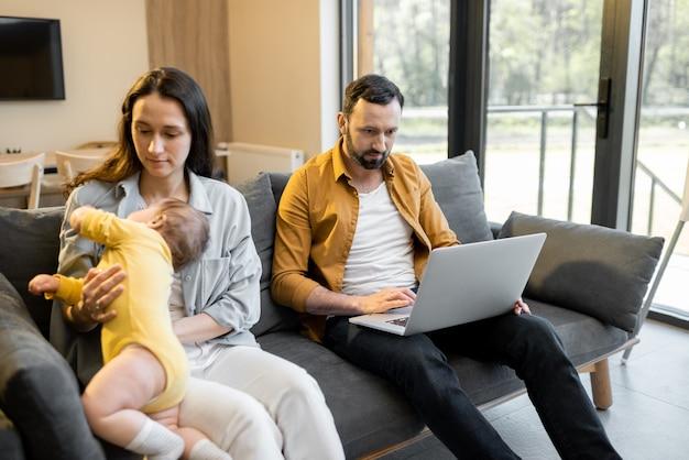 Мужчина работает из дома с женой и маленьким сыном