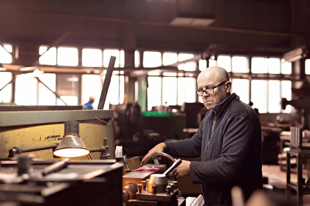 A man works at the machine at the factory