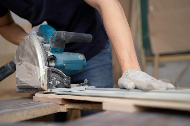Человек работает над лобзиком в мастерской