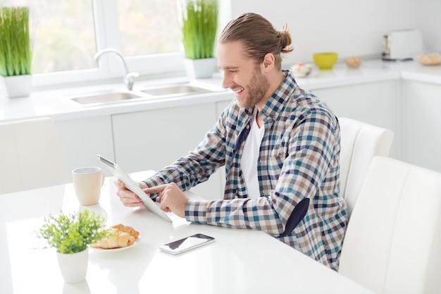 남자 태블릿에 작동하고 아침 식사를 먹는다
