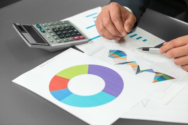 남자는 그래픽으로 작동합니다. 진행 차트. 진행 보고서. 새로운 전략 구축.