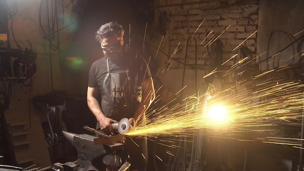Man works with molten metal in the forge.