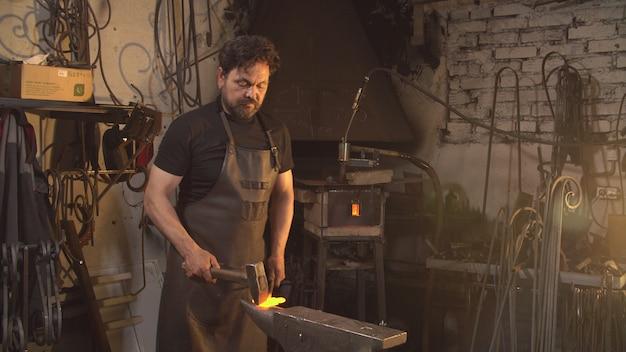 남자는 단조에서 녹은 금속으로 작동합니다.
