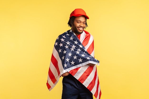 Man wrapped in american flag looking at camera and smiling proud of his country