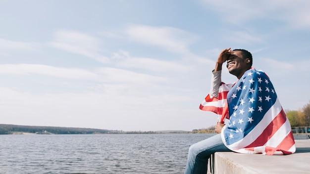 L'uomo avvolto nella bandiera americana seduto penzoloni piedi e chiudendo gli occhi dal sole