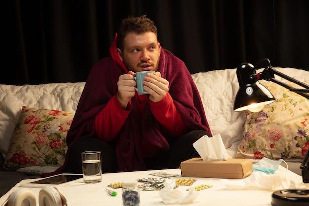 Человек, завернутый в плед, выглядит больным, чихает и кашляет, сидя дома в помещении