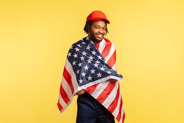 Человек, завернутый в американский флаг, смотрит в камеру и улыбается, гордясь своей страной