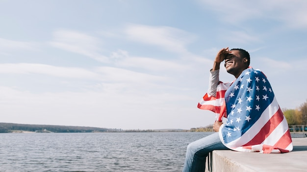 Человек, завернутый в американский флаг, сидит, свесив ноги и закрывая глаза от солнца
