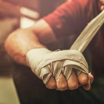 ボクシングの準備ができて、彼の手を包む男