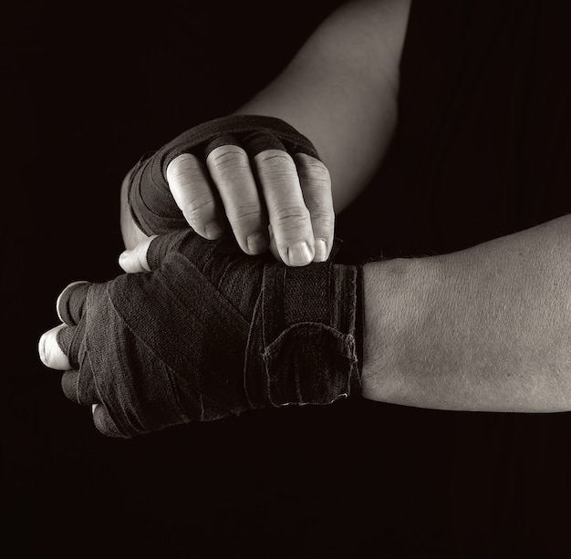 Man wraps his hands in black textile bandage for sports