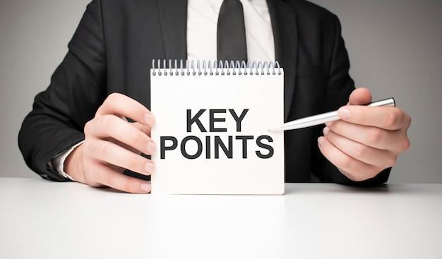 남자는 은색 펜과 손에 key points라는 텍스트가 있는 카드를 들고 노트북에 씁니다. 회색 배경, 전면 보기입니다. 비즈니스 및 교육 개념입니다.