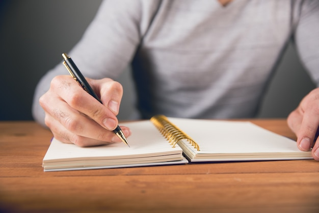 A man writes in a notebook and next to a piggy bank