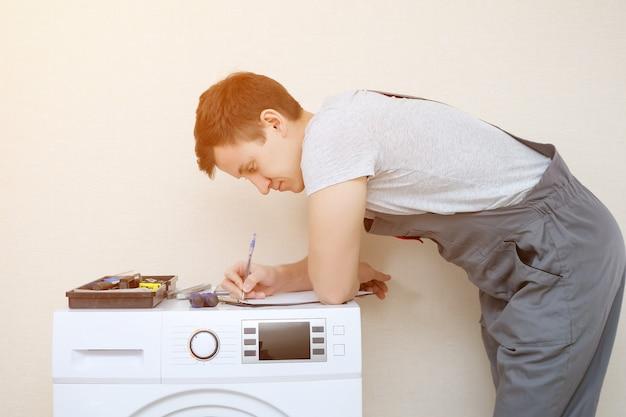 남자는 현대 세탁기를 검사하는 클립보드에 씁니다.