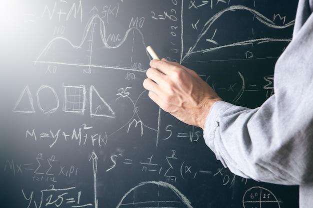 A man writes with chalk on a blackboard