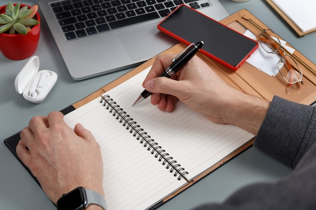 Man writing in agenda on a grey office desk close up