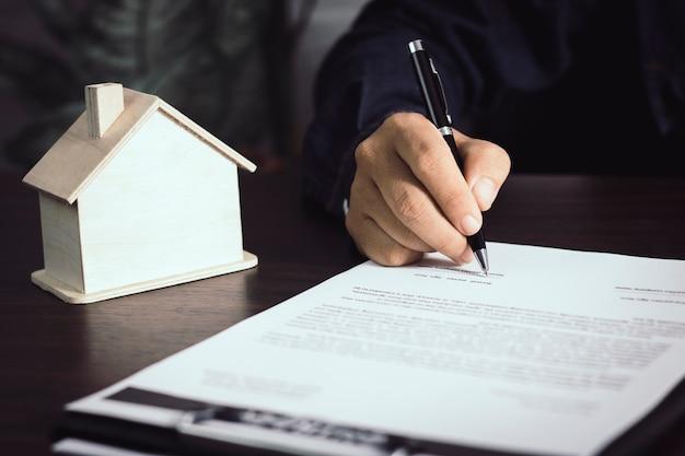 家の契約書を書いて署名する男