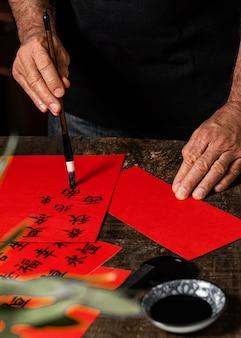Uomo che scrive simboli cinesi su carta rossa