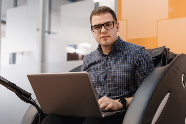 Man writing code while sitting in armchair in the office