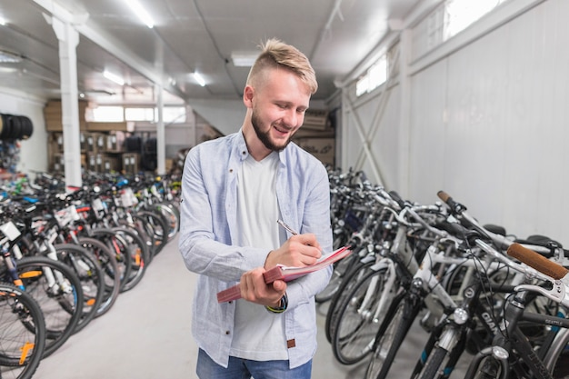 Man writing on document in bicycle shop