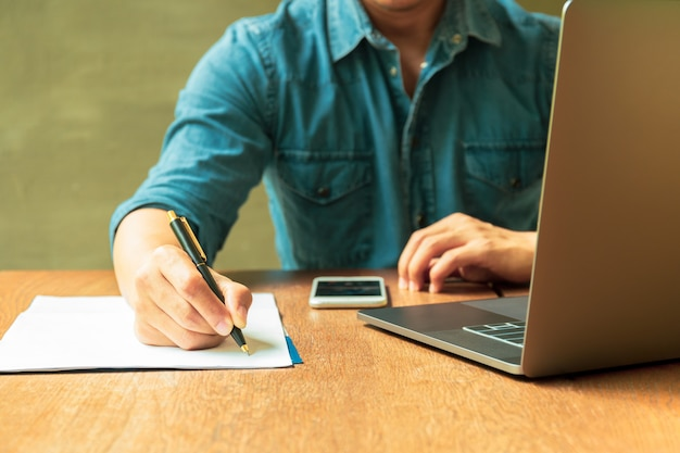 Man writing document on paperwork with laptop and cell phone on wooden desk