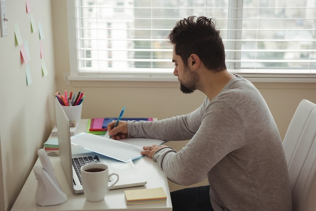 Man writing on document while sitting at desk