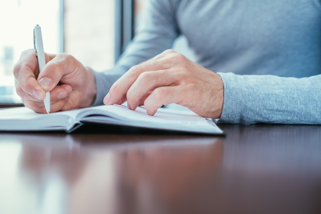 手帳を隠して書いている男。計画と情報の構造化。