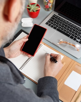 Man writing monday in agenda and using cell phone on a grey office desk close up