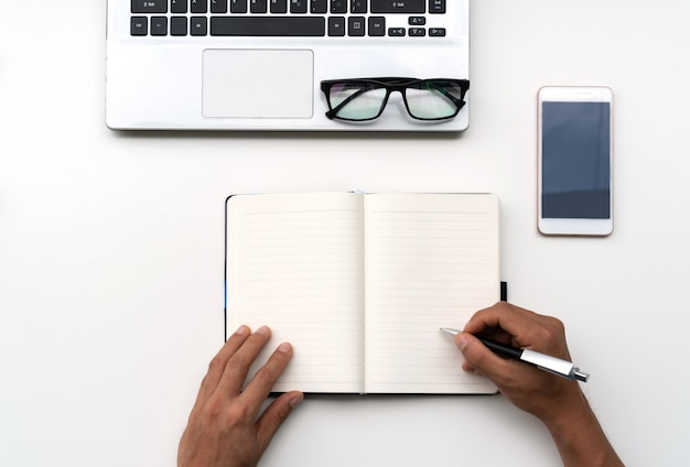 Man writing on notebook with mobile phone, computer and glasses on white table, top view, copy space for text.