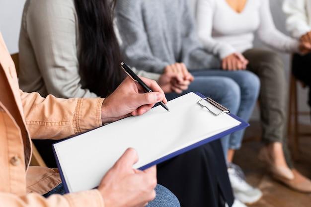 集団療法セッションでクリップボードに書いている男性
