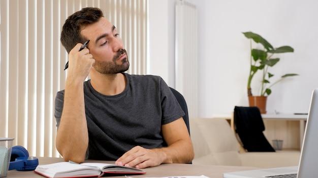 彼の机でノートに書いている男。紙に考えを置く。
