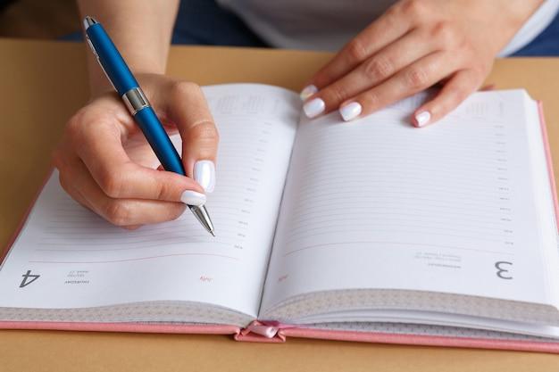 Человек пишет синей серебряной металлической ручкой в розовом дневнике