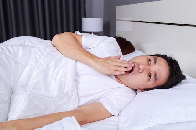 Мужчина зевает и его жена спит на кровати