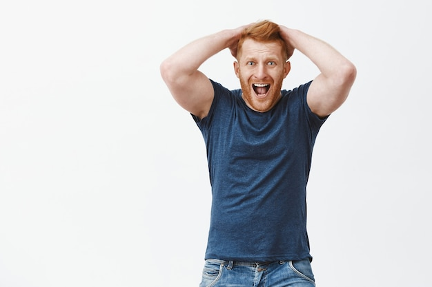 Man yelling from regret and shock. handsome mature redhead guy in despair, touching hair, screaming and staring shocked and devestated, feeling disappointment over gray wall