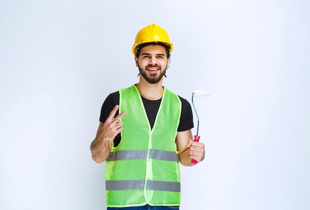 Uomo in marcia gialla che tiene un rullo di pittura e si sente soddisfatto.