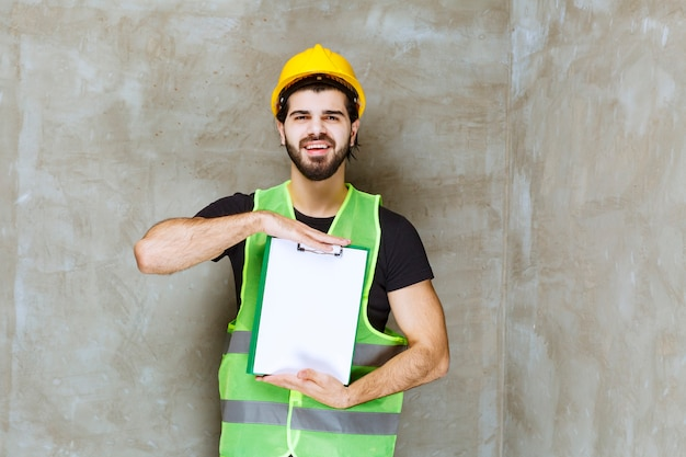 Uomo con casco giallo e attrezzatura in possesso di un piano di progetto e sembra positivo